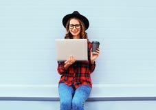 塑造使用有咖啡杯的年轻微笑的妇女便携式计算机休息户外在城市,穿黑帽会议红色方格的衬衣 免版税库存图片