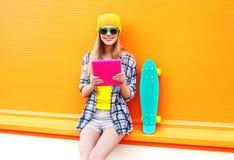 塑造使用片剂个人计算机的凉快的女孩在有滑板的城市在五颜六色的桔子 免版税库存照片