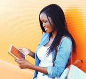 塑造使用片剂个人计算机的年轻人微笑的非洲妇女在五颜六色的桔子的城市 库存图片
