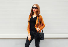 塑造俏丽妇女佩带太阳镜在灰色的棕色夹克黑色提包 库存照片