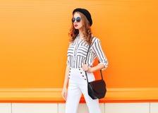 塑造俏丽的妇女佩带的黑帽会议太阳镜白色裤子和提包传动器在五颜六色的桔子 库存图片