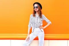 塑造俏丽的妇女模型佩带的黑帽会议太阳镜在五颜六色的白色裤子 免版税库存照片