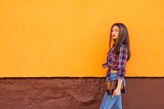 塑造俏丽的微笑的妇女画象有片剂的对五颜六色的橙色墙壁 库存照片