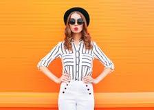 塑造俏丽的魅力妇女佩带的黑帽会议太阳镜在五颜六色的桔子的白色裤子 免版税库存照片