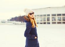 塑造冬天相当白肤金发的妇女佩带的夹克帽子太阳镜 免版税图库摄影