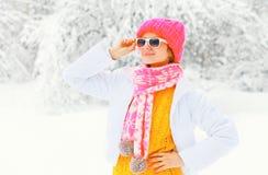 塑造冬天画象穿在多雪的少妇一条五颜六色的被编织的帽子围巾 免版税库存图片