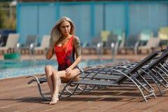 塑造华美的性感的女孩室外照片有金发的在泳装松弛近的游泳池 免版税库存图片
