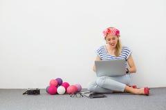 塑造博客作者坐与计算机的地板 免版税库存图片