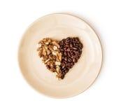 塑造咖啡豆和被剥皮的核桃的心脏在板材, Val 免版税图库摄影