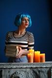 塑造在摆在与书和蜡烛的蓝色假发 关闭 可能 免版税库存照片