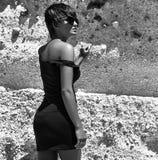 塑造在摆在沙子岩石附近的夏天蓝色礼服 免版税图库摄影