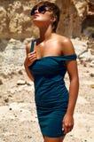 塑造在摆在沙子岩石附近的夏天蓝色礼服 库存照片