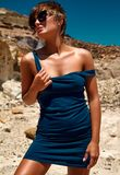 塑造在摆在沙子岩石附近的夏天蓝色礼服 免版税库存照片