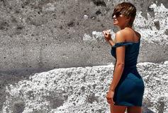 塑造在摆在沙子岩石附近的夏天蓝色礼服 库存图片
