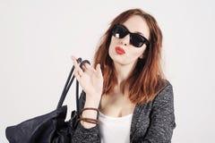 塑造在摆在演播室的精密衣裳的年轻时髦模型 佩带的太阳镜和提包 免版税图库摄影