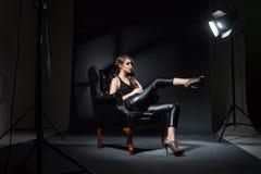 塑造在摆在黑皮椅的聚光灯在演播室 库存图片