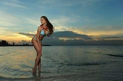 塑造在有珊瑚项链摆在的比基尼泳装性感在空的海滩 图库摄影