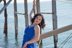 塑造在海边在与长的蓝色礼服的冬天 免版税图库摄影