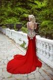 塑造在红色褂子的典雅的白肤金发的妇女模型有长的火车的  免版税库存图片