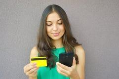 塑造在网上买与巧妙的电话和信用卡的女孩隔绝在紫罗兰色背景 免版税库存照片