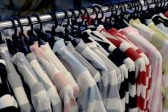 塑造在衣物机架,衣物时尚挂衣架,在夜农贸市场时尚的五颜六色的晒衣架的衣裳 免版税库存图片
