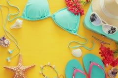 塑造在黄色木背景的女性泳装比基尼泳装 夏天海滩假期概念 免版税库存照片