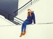 塑造坐在白色墙壁的冬天城市的白肤金发的妇女 库存照片