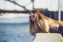 塑造太阳镜的妇女在河堤防 美丽的女孩室外纵向年轻人 愉快的年轻人微笑妇女阳光ci 库存照片