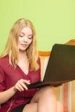 塑造妇女坐沙发使用个人计算机膝上型计算机 库存照片