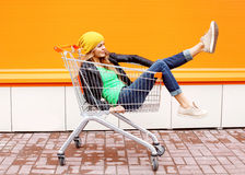 塑造妇女骑马获得乐趣在购物台车推车 免版税库存图片