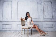 塑造年轻美丽的妇女射击坐在古色古香的椅子的白色短的礼服的 免版税图库摄影