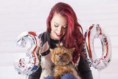 塑造庆祝她的与她的小狗的俏丽的妇女生日 库存照片