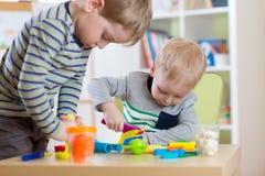 塑造彩色塑泥,孩子的孩子戏剧铸造五颜六色的黏土面团 一起使用的学龄前儿童 免版税库存图片