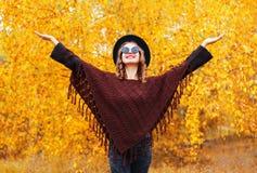 塑造微笑的妇女佩带的黑帽会议太阳镜和被编织的雨披在秋天晴朗的黄色叶子 库存图片
