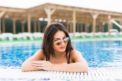 塑造性感的美丽的女孩照片放松在游泳池的典雅的比基尼泳装的 夏天职业 免版税库存照片