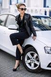 塑造性感的美丽的妇女室外照片有黑发的在黑摆在豪华汽车的皮夹克和太阳镜 免版税库存照片
