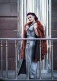 塑造性感的魅力妇女室外照片有戴着豪华皮大衣和皮手套的黑发的 免版税库存照片