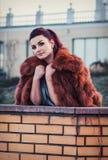 塑造性感的魅力妇女室外照片有戴着豪华皮大衣和皮手套的黑发的 免版税库存图片