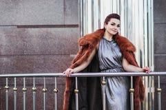 塑造性感的魅力妇女室外照片有戴着豪华皮大衣和皮手套的黑发的 免版税图库摄影