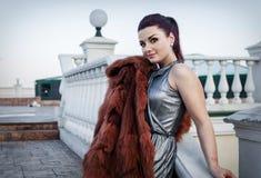 塑造性感的魅力妇女室外照片有戴着豪华皮大衣和皮手套的黑发的 库存图片