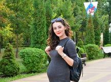 塑造愉快室外的一个怀孕的少妇的画象 免版税库存图片