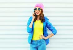 塑造愉快的凉快的微笑的女孩谈话在五颜六色的衣裳的智能手机在戴桃红色帽子黄色太阳镜的白色背景 免版税图库摄影