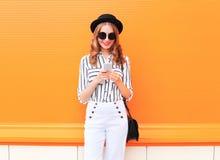 塑造愉快的年轻微笑的妇女模型使用智能手机在五颜六色的桔子的佩带的黑帽会议白色裤子 免版税库存图片