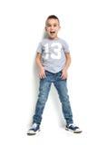 塑造愉快T恤杉的牛仔裤的美丽的小男孩站立和 免版税库存图片