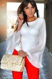 塑造拿着金黄袋子的红色裤子白色女衬衫的美丽的肉欲的深色的妇女 库存图片