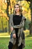 塑造摆在典雅的外套的美丽的妇女照片户外 库存照片
