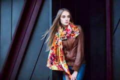 塑造摆在对现代墙壁的妇女佩带的皮革外套和围巾 库存照片