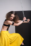 塑造摆在演播室的美丽的女孩照片 穿着黄色短裤,染黑起动 在拿着链子的乳房的皮带 免版税库存图片