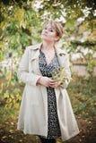 塑造摆在秋天公园的可爱的少妇 免版税图库摄影