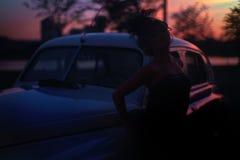 塑造摆在老汽车附近的减速火箭的样式的女孩 免版税图库摄影
